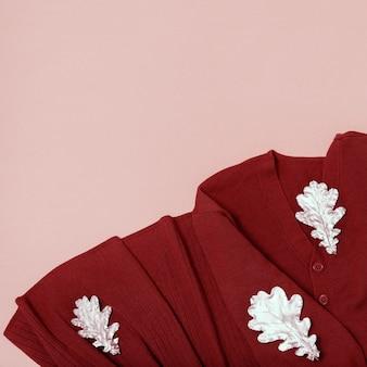 Robe en tricot de mode en terre cuite, feuilles d'automne dorées sur fond de papier jaune avec espace de copie. lifestyle vêtements de confort d'automne. mise à plat, couleur pastel.