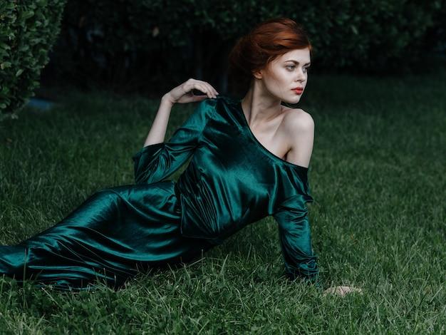 Robe verte de luxe femme se trouve sur l'herbe carnaval princesse