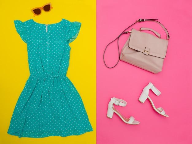 Robe verte menthe, sac à main, chaussures blanches et lunettes roses. fond rose-jaune vif. concept à la mode