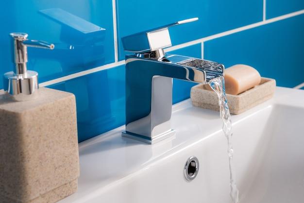 Robinet en acier neuf et moderne avec lavabo en céramique dans la salle de bain