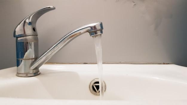 Robinet ancien et sale et lavabo en céramique blanche, concept de nettoyage, de réparation ou de remplacement d'une salle de bain, toilettes.