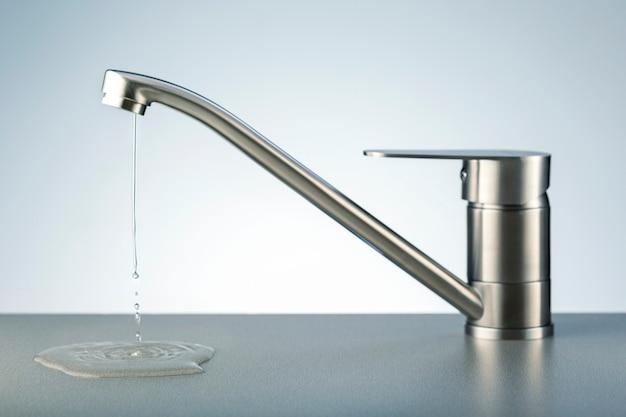 Robinet d'eau qui fuit endommagé. fuite d'eau, concept d'économie.