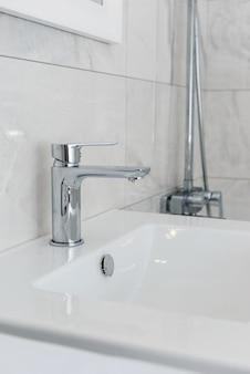 Robinet avec un lavabo dans la salle de bain avec des carreaux gris. rénovation dans la salle de bain.