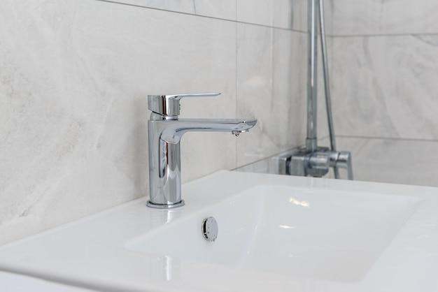 Robinet avec un lavabo dans la salle de bain avec des carreaux gris.