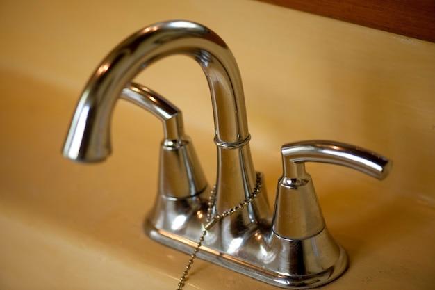 Robinet de salle de bain chrome à double poignée et robinets avec une chaîne de prise sur un bassin jaune