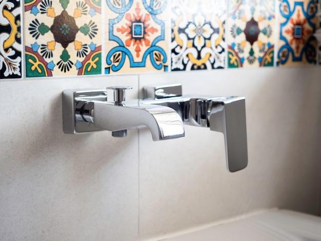 Robinets modernes en acier inoxydable pour baignoire près de magnifiques carreaux de mosaïque de style marocain.