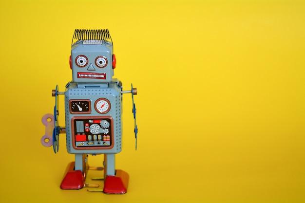 Robot jouet vintage en étain isolé sur fond jaune.