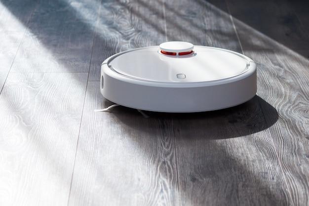Robot nettoyant blanc nettoyage sur plancher en bois stratifié aux beaux jours. concept de technologie intelligente.