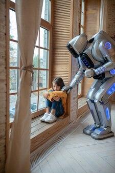 Robot parlant à la fille assise à la fenêtre
