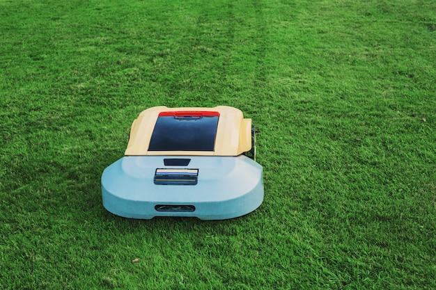Robot tondeuse à gazon sur l'herbe verte