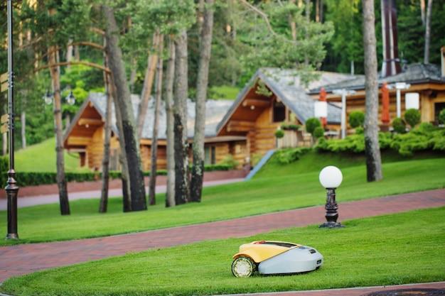Robot tondeuse à gazon et maisons en bois