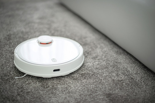 Les robots aspirent les nettoyeurs sur tapis dans le salon pour nettoyer les poils d'animaux et la poussière. robot aspirateur travaillant sur une surface recouverte de moquette.