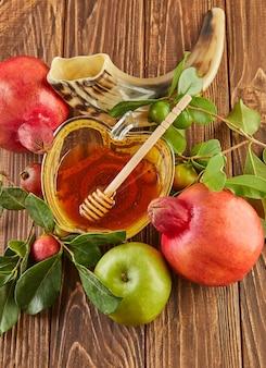 Roch hachana - concept de vacances du nouvel an juif. un bol en forme de pomme avec du miel, de la grenade, du shofar sont des symboles traditionnels de la fête