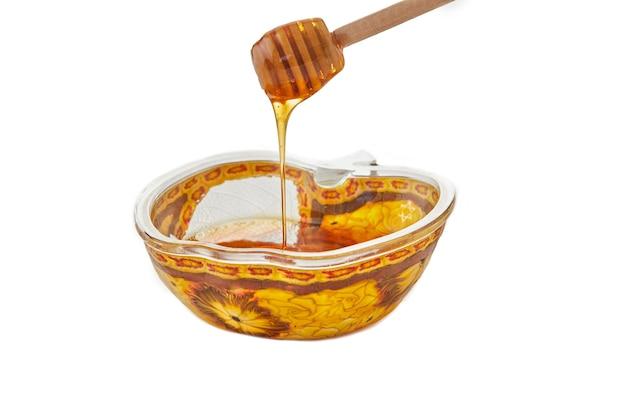 Roch hachana est le concept de la fête du nouvel an juif. un bol en forme de pomme avec du miel et un bâton sur fond blanc