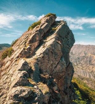 Un rocher pointu contre le ciel bleu. roche pointue et pointue. crête de montagne pointue rocheuse avec un gouffre.