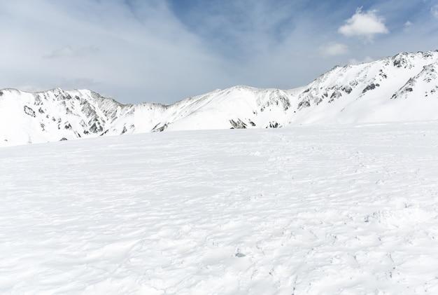 Rochers sur la neige couverte de montagne sous le ciel bleu