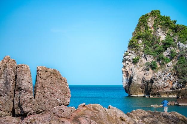 Rochers, pêcheur, mer et ciel bleu