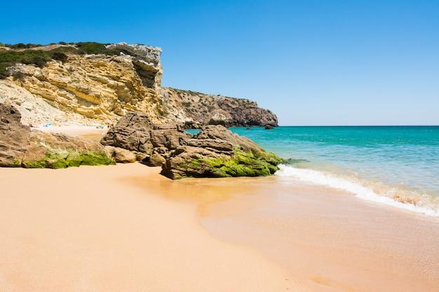 Rochers sur la plage de sable de praia do amado, portugal