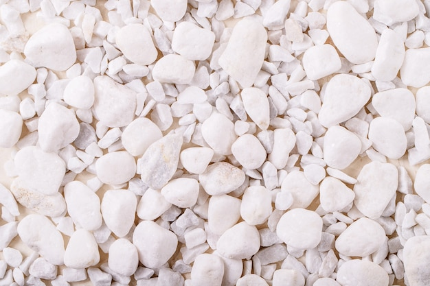 Roches et cailloux décoratifs blancs sur fond de texture blanche. mise en page créative de la nature