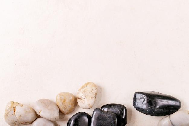 Roches et cailloux décoratifs blancs et noirs sur fond de bois gris. mise en page créative