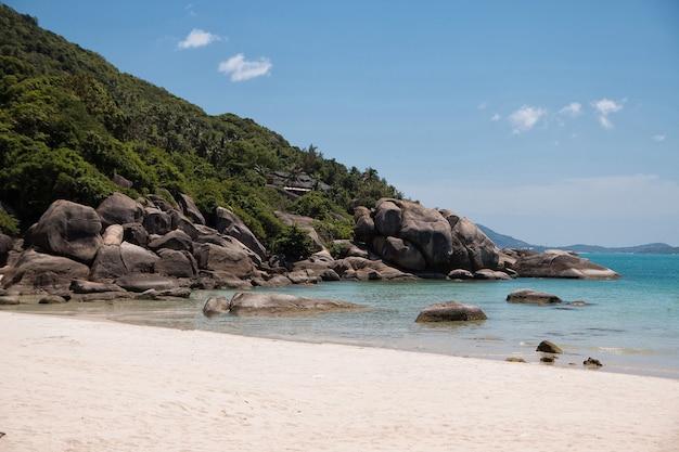 Roches de granit d'eau turquoise et arbres tropicaux dans le sable blanc