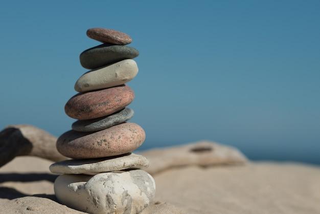 Des roches parfaitement équilibrées les unes sur les autres sur le sable montrant le concept d'harmonie