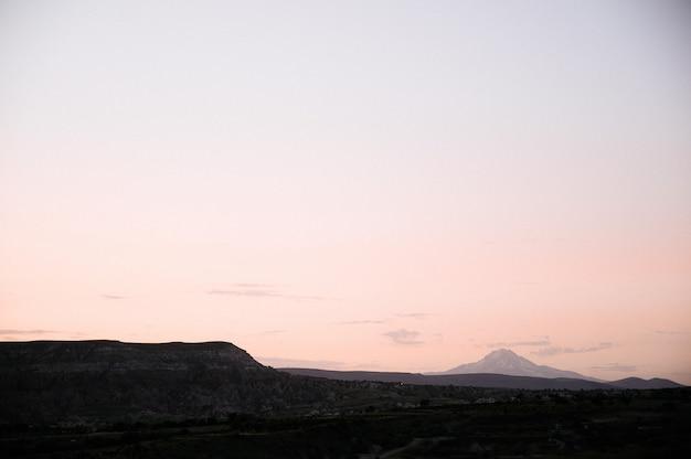 Des roches ressemblant à des champignons dramatiquement éclairées par un coucher de soleil en cappadoce, turquie