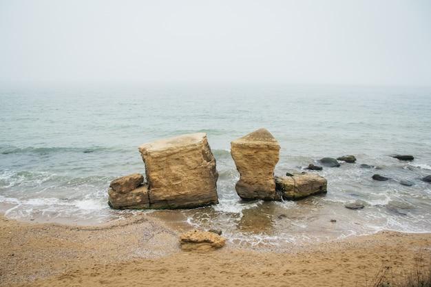 Roches de sable sur la plage sur fond de mer