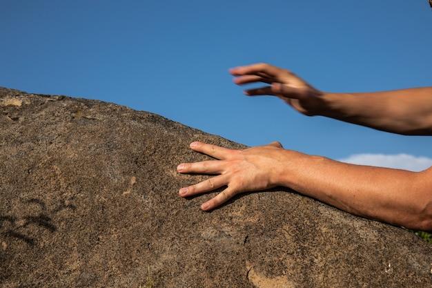 Rock climber's hands on handhold sur fond de ciel bleu.