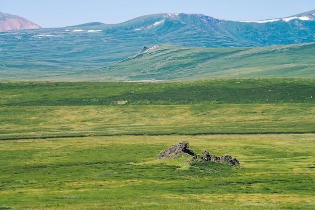 Rock dans la vallée verte contre les montagnes géantes de neige sous un ciel bleu clair. prairie avec une riche végétation de hautes terres au soleil. magnifique paysage de montagne ensoleillé de nature majestueuse.