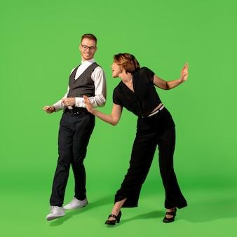 Rock n roll. jeune femme à l'ancienne danse isolée sur fond de studio vert. mode d'artiste, concept de mouvement et d'action, culture des jeunes, retour de la mode. jeune homme et femme élégant.