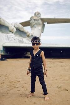 Rocker boy un enfant en vêtements noirs se dresse dans le contexte d'un avion abandonné sur la plage