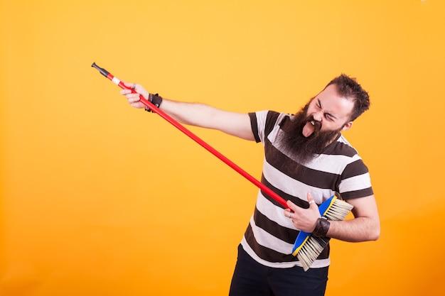 Rockstar barbu drôle jouant de la guitare virtuelle avec un balai sur fond jaune. bel homme. cheerul homme.