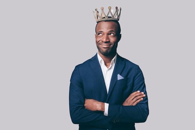 Roi? beau jeune homme africain en couronne et veste décontractée intelligente faisant une grimace en se tenant debout