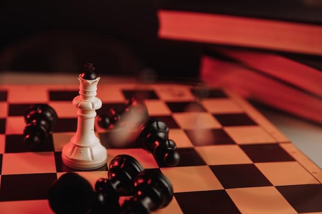 Roi blanc debout sur un échiquier autour du thème du leadership des figures tombantes
