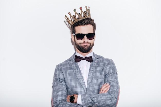 Roi du style. jeune bel homme ricanant portant un costume et une couronne en gardant les bras croisés et en regardant la caméra en se tenant debout sur fond blanc