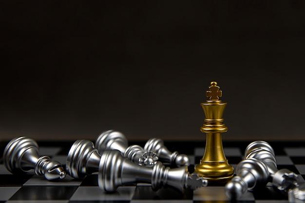 Le roi d'échecs en or debout au milieu des échecs en argent qui tombent.