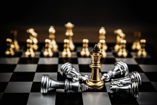 Roi d'échecs d'or debout face à au milieu des échecs en argent tombant