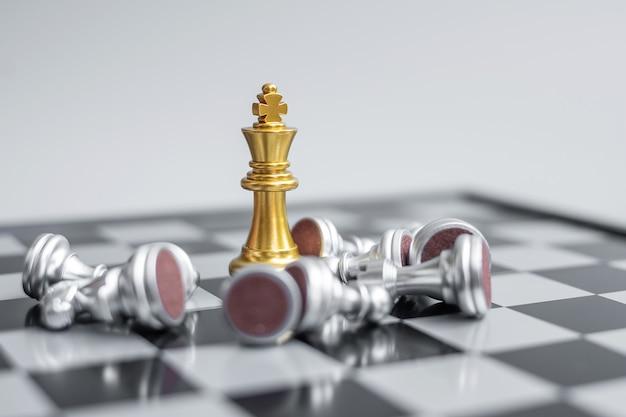 Le roi des échecs en or se démarque de la foule de l'ennemi lors de la compétition sur l'échiquier.