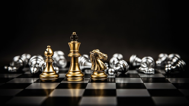 Roi et évêque et chevalier d'échecs debout sur un échiquier.