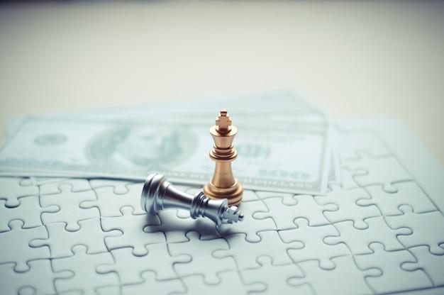 Le roi d'or aux pièces d'échecs gagne avec un puzzle, un fond de billets pour les affaires et les finances.