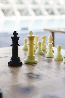 Rois d'échecs noir et blanc confrontés entre des pièces floues sur une planche de bois.