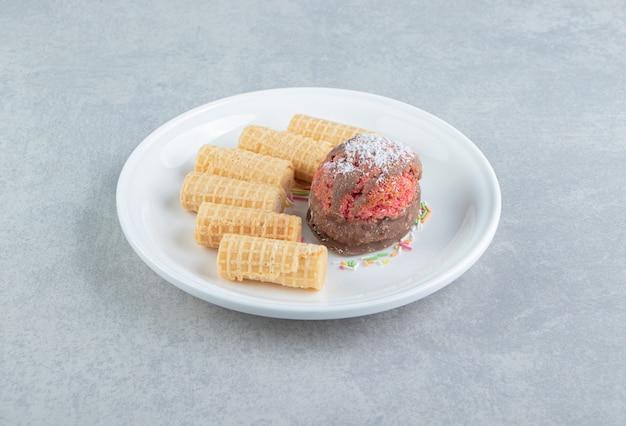 Rôles de gaufres en tranches sucrées avec gâteau sur une assiette blanche.