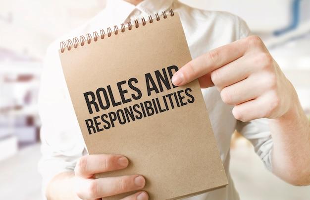 Rôles et responsabilités du texte sur le bloc-notes de papier brun dans les mains de l'homme d'affaires au bureau.