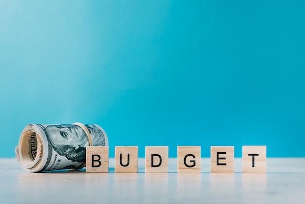Rolled dollars et mot budget sur fond bleu