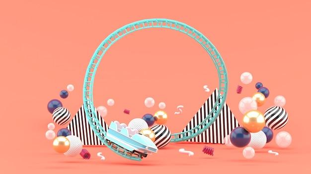 Un roller coaster bleu parmi les boules colorées sur rose. rendu 3d.