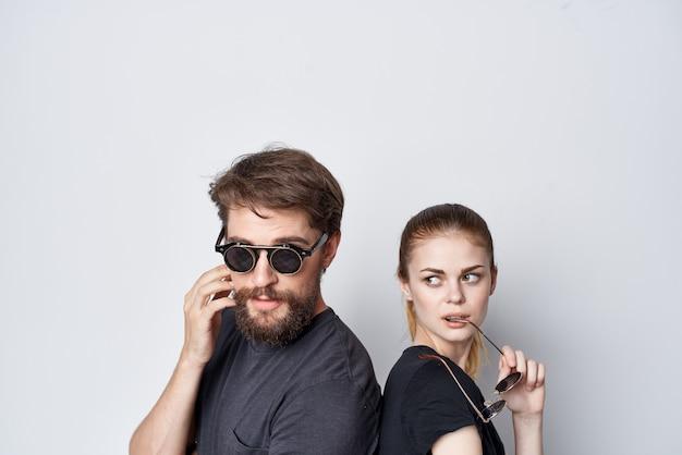 Romance de communication d'amitié homme et femme à la mode portant des lunettes de soleil fond clair