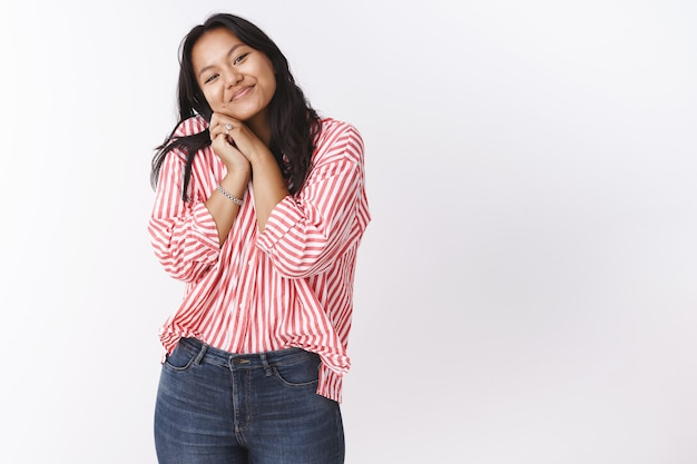 Romance, saint valentin et concept d'amour. tendre jeune femme asiatique charmante s'appuyant sur l'épaule mignonne et pressant les paumes ensemble souriant du bonheur comme ravie d'un joli bouquet de fleurs