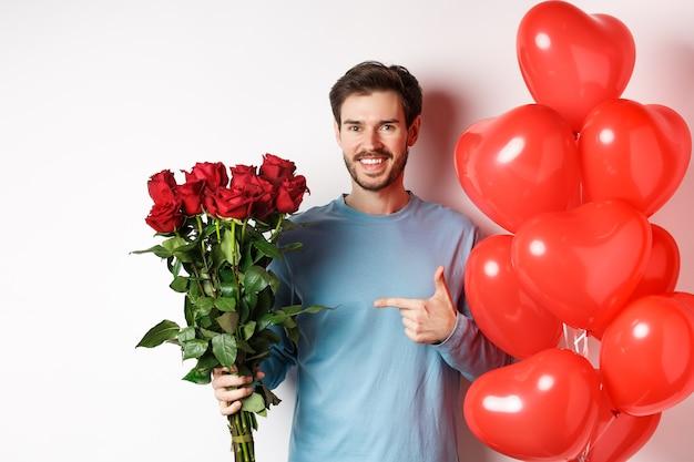 Romance de la saint-valentin. heureux jeune homme avec des fleurs et des ballons coeur sortant avec lon. gars souriant pointant sur le bouquet de roses rouges, debout sur blanc