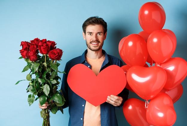 Romance de la saint-valentin. petit ami avec bouquet de roses rouges et ballons coeur souriant, apportez des cadeaux pour l'amant à la date de la saint-valentin, debout sur fond bleu.
